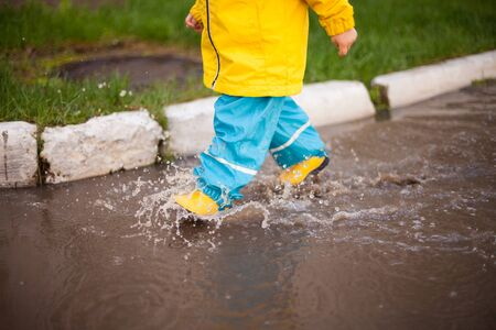 spring walks in any weather. the child runs through the puddles in rubber boots and a waterproof suit, splashing water in all directions. Happy childhood with fun walks Imagens