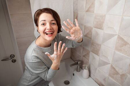 positive and laughing woman washes her hands with soap in the bathroom. Girl shows soaped hands and holds for 20 seconds. stop sorrow Hand disinfection during quarantine of the coronavirus pandemic. Stock Photo