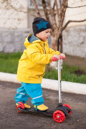 a boy in a protective water suit rides a scooter through puddles. spring walks in the fresh air.