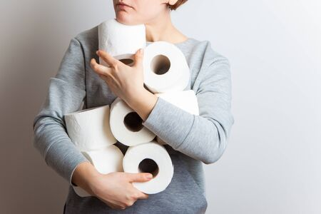 People are stocking up toilet paper for home quarantine from crownavirus. Woman holds many rolls of toilet paper. panic in stores.