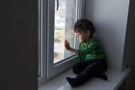 quarantine. a little boy sits in a window-sill and looks out the window bored. longing for fresh air and walks along the street. Forced home during quarantine due to the coronavirus pandemic. Stok Fotoğraf