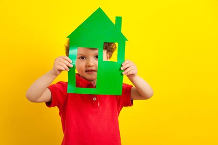 The boy is hiding in a cardboard house. child in a bright red jacket. On a bright yellow studio background holds a green house. stay home.