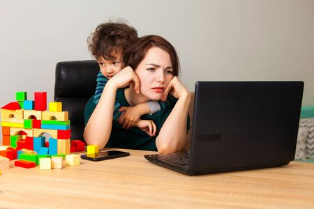 Tired woman at a laptop working at home. A boy, a child assembled a house of cubes and hangs on his mothers neck demanding attention to himself. Stock Photo