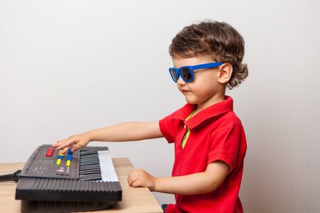 the child arranges a concert at home for parents playing the synthesizer. Imagine the street and the scene in sunglasses. dull and funny quarantine at home