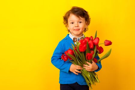 A mothers Mothers Day gift. Cute curly kid stands with a bouquet of flowers and smiles.