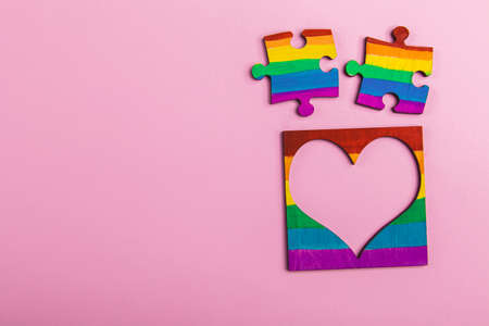 mock-up LGBT symbolism in the form of a rainbow two puzzle and heart frame. A place for photography and text on a pink background.