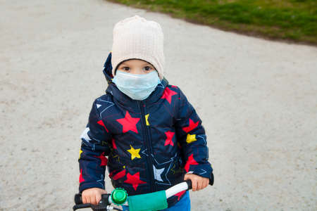 A child walks in a mask on the street on a bicycle. Relaxation of quarantine, lifting restrictions. The baby breathes fresh air outside