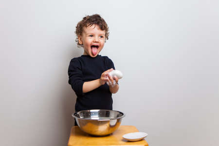 Funny emotional baby dabbles, washes his hands with soap and shows tongue. Studio white background