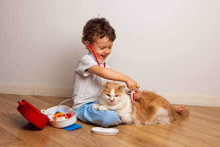 funny curly kid in a medical mask and glasses with a stethoscope on his neck plays a doctor with a cat. The child wants to inject the cat with a toy syringe.