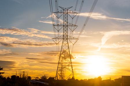 megawatts: High voltage transmission lines on orange and blue sky, sunrise period