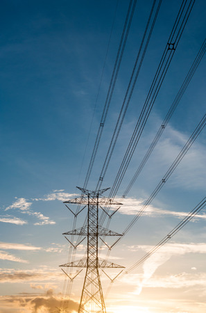 megawatts: High voltage transmission lines isolated on orange sky, sunrise period Stock Photo