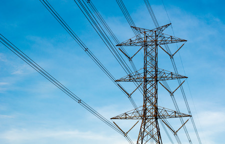 megawatts: High voltage transmission lines isolated on blue sky background