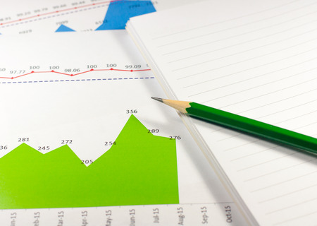 everyday jobs: financial graph chart with notebook and green pencil. business concept