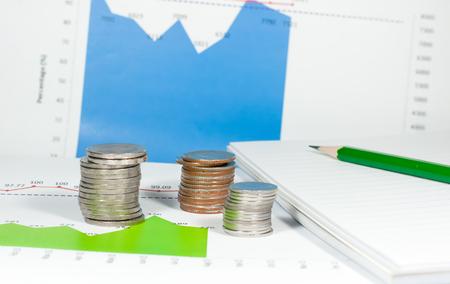 鉛筆とノート、青い緑グラフとチャートの背景のコイン。お金と金融の概念。 写真素材 - 47211315