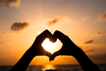 Love shape hand silhouette in sunset or dunrise period Stock Photo