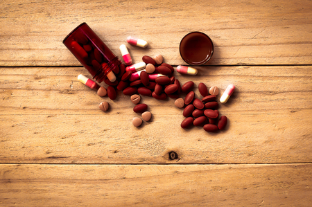 reliever: Pill spilling out of brown color pill bottle on old wood background