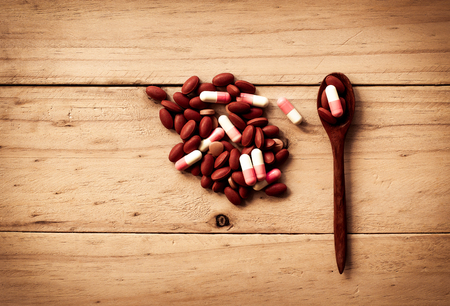 reliever: Pill spilling with old wooden spoon on wooden background Stock Photo