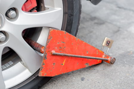 parking violation: red color of clamp is locked front wheel of illegally parked car