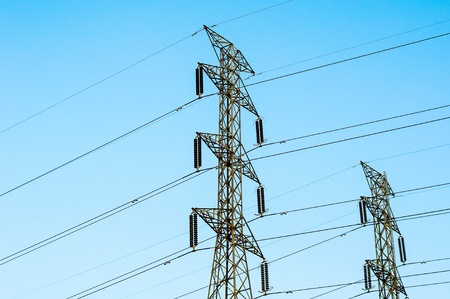 megawatts: The High voltage transmission lines isolated on blue sky background