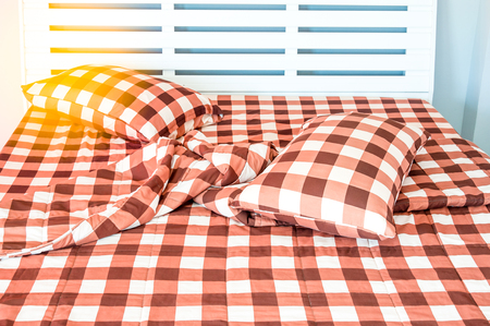 closeup of bed in small bedroom with warm light Stock Photo