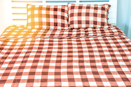 natty: closeup of bed in small bedroom with warm light Stock Photo