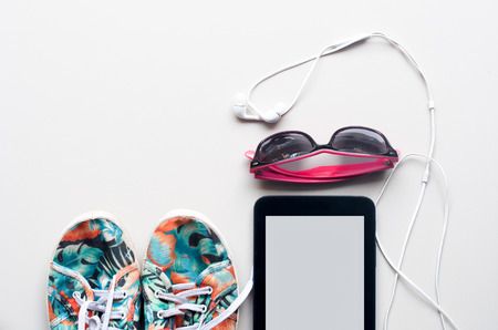 plimsoll: colorful Canvas shoe, white Earphone with sunglasses and Tablet on white background. accessories for travelling Stock Photo