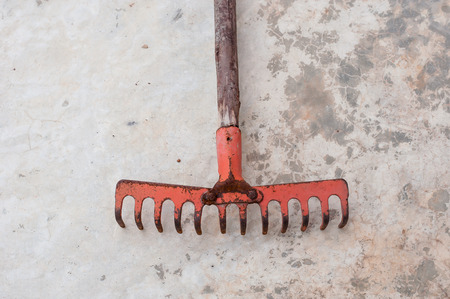 replant: red old rake on the cement floor ground Stock Photo