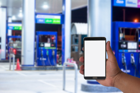 hand of man hold mobile phone over blurred car filling station with bokeh light Background