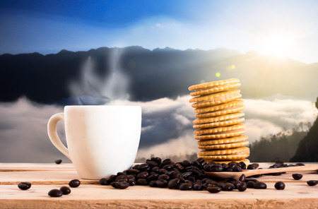 coffee beans and cup of coffee with cracker on wooden table in nature view. coffee break