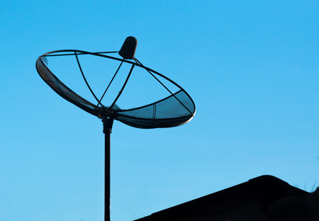 silhouette of satelite dish for television in b;ue sky background Stock Photo