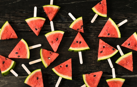watermelon slice popsicles on a rustic wood background