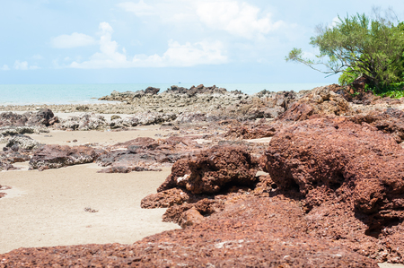 midday: red stone and rock on the sand beach in clear blue sky and noon time period