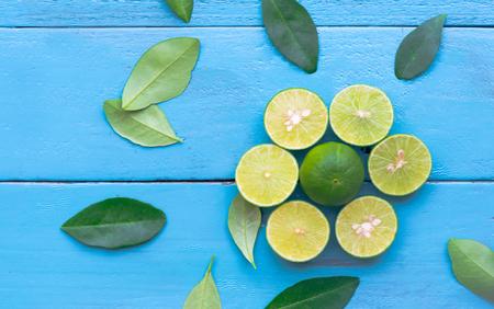 Lime lemon are half cut on blue wooden background. Leadership concept
