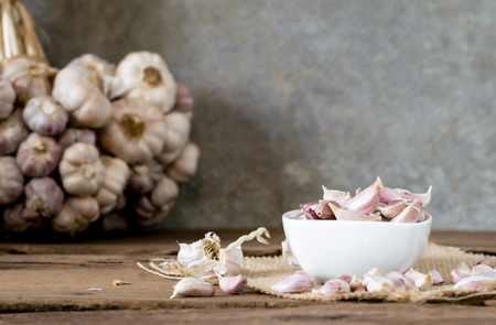 garlic in bowl on old wooden table with old wallpaper and garlic bunch background