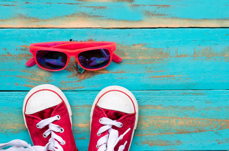 red sneakers with pink sunglasses on old blue wooden floor background. copy space for graphic designer