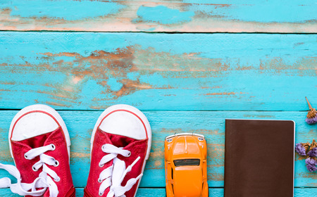 red sneakers with orange car and passport book on old blue wooden floor background. copy space for graphic designer Standard-Bild