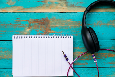 notebook with black headphone with  line jack for connect on old blue wooden floor background.