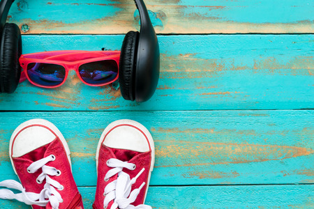 red sneakers with pink sunglasses and headphone on old blue wooden floor background. copy space for graphic designer Standard-Bild