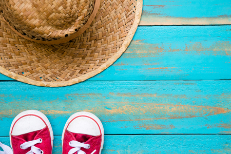 red sneakers with weave hat on old blue wooden floor background. copy space for graphic designer