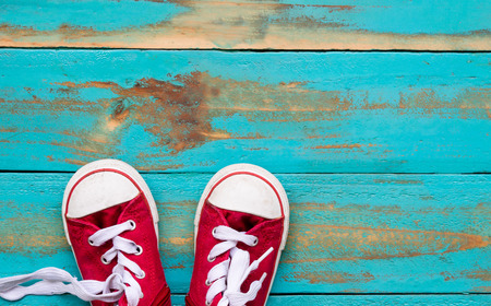 red sneakers on old blue wooden floor background. copy space for graphic designer