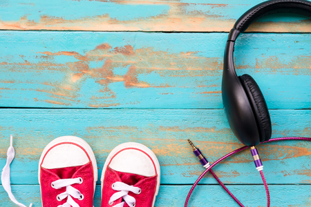 red sneakers with black headphones on old blue wooden floor background. copy space for graphic designer