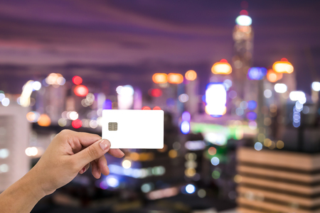 hand hold blank card on cityscape bokeh, Blurred Photo, cityscape at twilight time