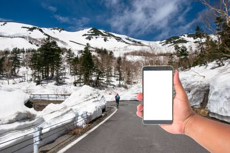 hand hold mobile phone with a road of snow wall japan alps mountain, Japan