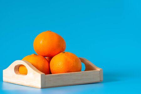 Summer of orange fruit in wood box on blue background