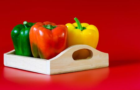 Summer of sweet bell pepper in wood box on red background Standard-Bild