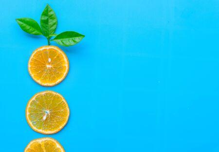 Summer of slice orange fruit with green Leaves on blue