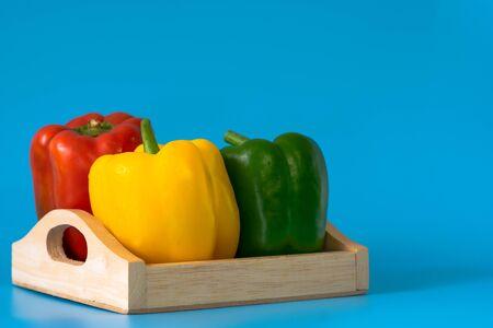 Summer of sweet bell pepper in wood box on blue background Standard-Bild