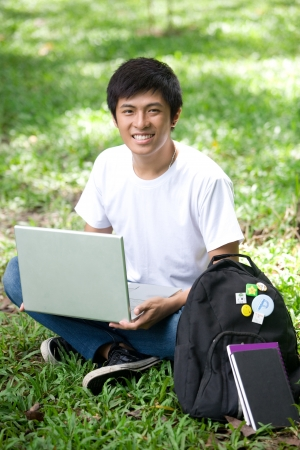 Young handsome Asian student with laptop and smile in outdoor photo