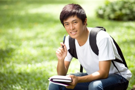 homework student: Young handsome Asian student open a book and smile in outdoor