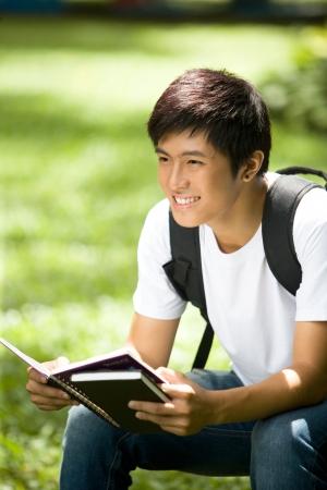 Asian male model: Thanh niên đẹp trai sinh viên châu Á mở một cuốn sách và mỉm cười ở ngoài trời